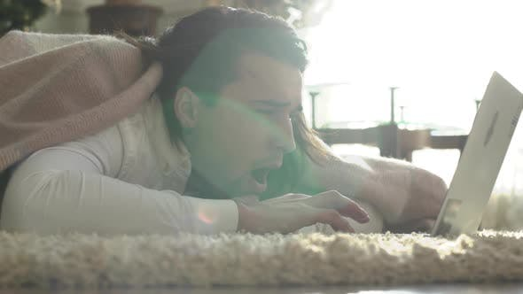 Thumbnail for Attractive Young Guy Yawns Lying on the Floor Covered with a Rug and Typing on a Laptop