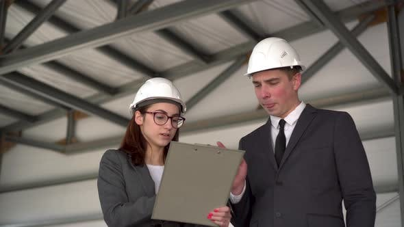 Thumbnail for Young Man and Woman in Helmets with Documents at a Construction Site. Bosses in Suits Are Discussing