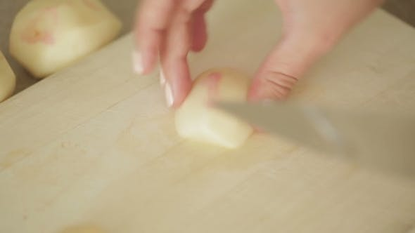 Thumbnail for Woman Slices a Potato On a Wooden Cutting Board