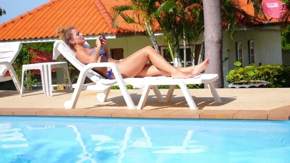 Thumbnail for Young Woman Holding a Smart Phone By The Pool