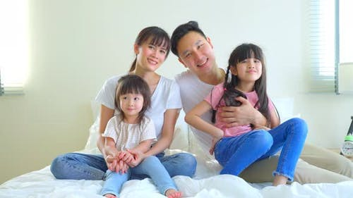 Portrait of Asian happy family smile and look at camera on bed together in bedroom at home.