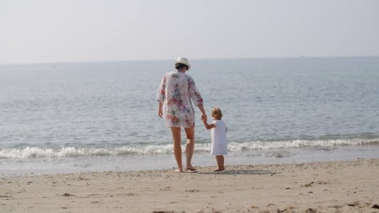 Thumbnail for Frau zu Fuß Hand in Hand mit Kind am Strand