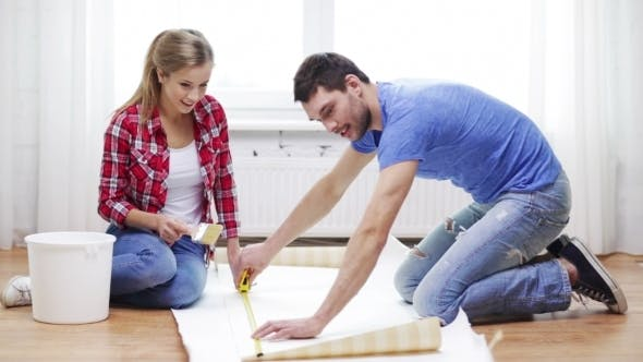 Thumbnail for Happy Couple Measuring Wallpaper At Home