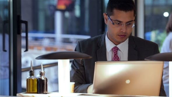 Cover Image for Businessman Working With Laptop In Cafe