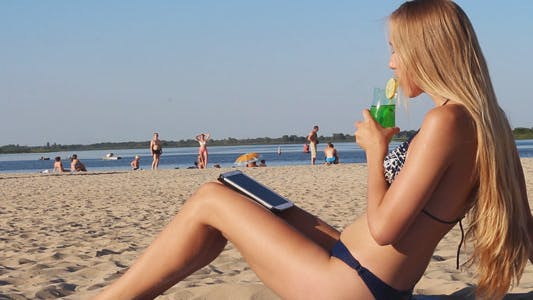 Thumbnail for Girl Drinks Cocktail and Using Tablet on the Beach