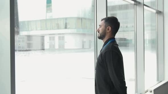 Un employé de bureau regarde les chutes de neige à l'extérieur de la fenêtre
