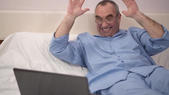 Thumbnail for Reaction of Success By Happy Man Using Laptop in Bed