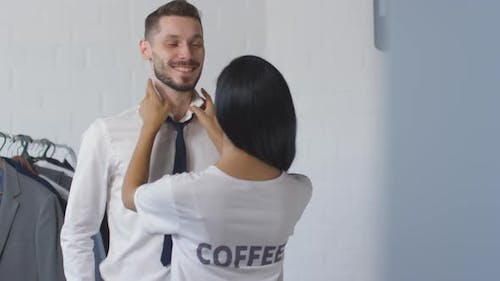Woman Tying Necktie for Husband in Morning