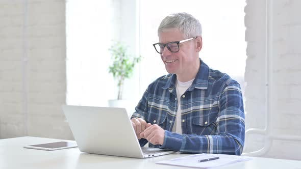 Thumbnail for Cheerful Casual Middle Aged Man Doing Video Chat on Laptop
