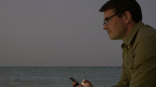 Thumbnail for Young Man Using Smart Phone By Sea In The Evening