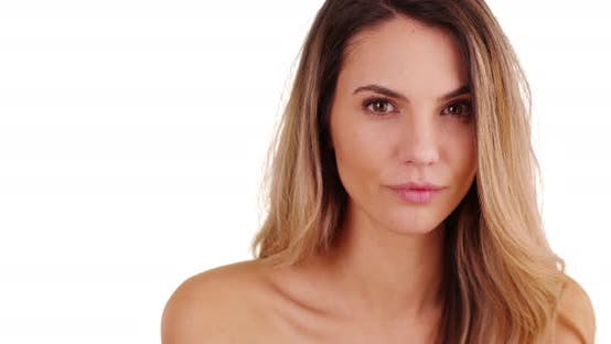 Thumbnail for Closeup of female millennial with healthy skin looking at camera in studio