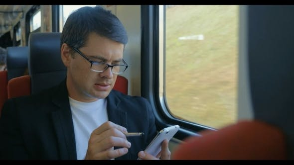 Thumbnail for Young Man Using Cell To Browse Online In Train