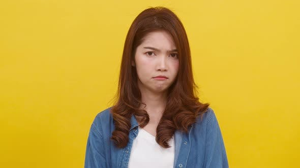 Asian female with positive expression, smiles broadly, dressed in casual over yellow background