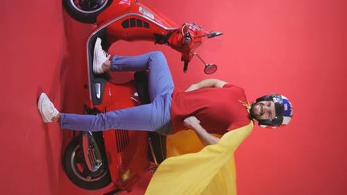 Cheerful Young Man in a Helmet and Raincoat Stands Next To a Scooter Isolated Red Background
