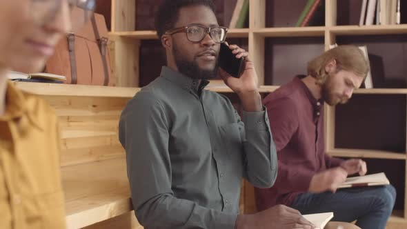 Confident Afro-American Man Talking on Smartphone in Cozy Hipster Cafe
