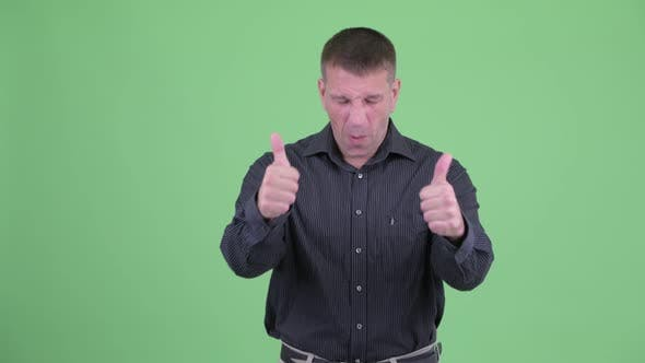 Thumbnail for Happy Macho Mature Businessman Giving Thumbs Up and Looking Excited