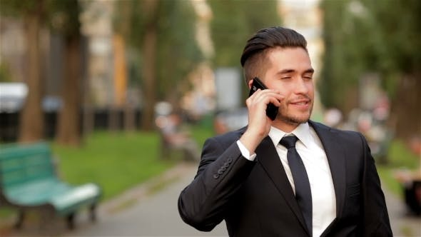 Thumbnail for Young Businessman Talking On Mobile Phone