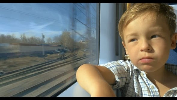 Thumbnail for Little Boy Looking Out Train Window On Sunny Day
