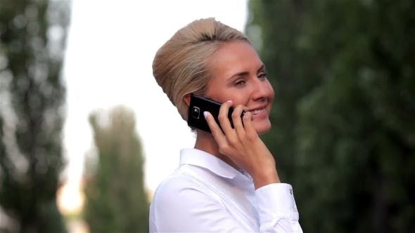 Cover Image for Beautiful Lady Talking On Mobile Phone Outdoors