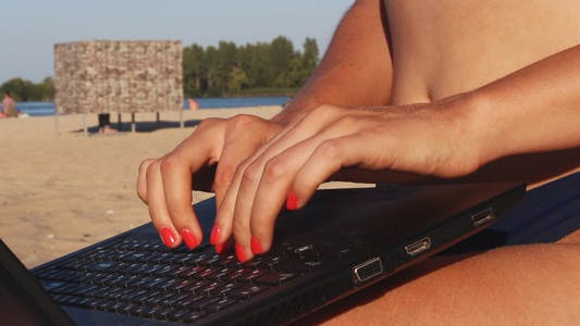 Thumbnail for Girl Typing on a Laptop on the Beach