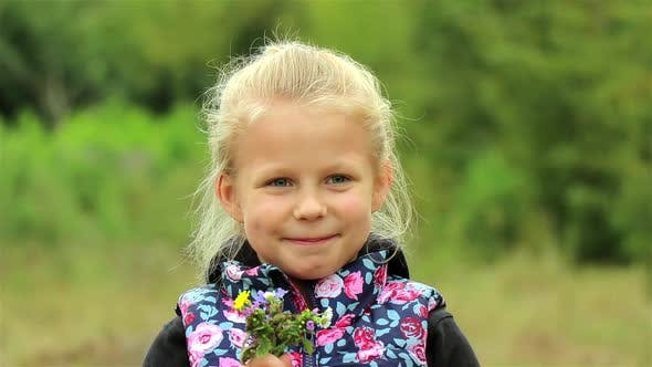 A portrait of a cute little girl. Beautiful Little girl enjoys the smell of flowers in the meadow.