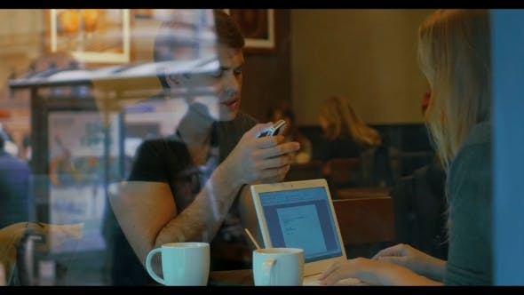 Thumbnail for Young People With Smart Phone And Laptop In Cafe