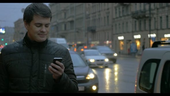Man With Cellphone In The Evening Rainy City