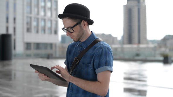Cover Image for Young Man Typing on Tablet