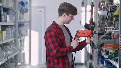 Man Choosing Drill in Hardware Store