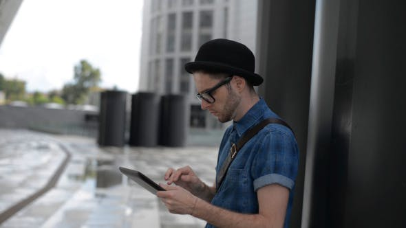 Thumbnail for Young Man Typing on Tablet