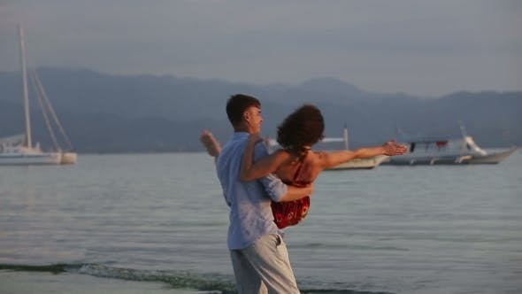 Thumbnail for Man Turns Girl On The Beach At Sunset