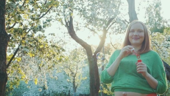 Thumbnail for Happy Pregnant Woman Blowing Bubbles In Bloomy