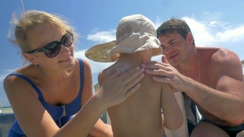 Parents Applying Suntan Lotion On Childs Skin