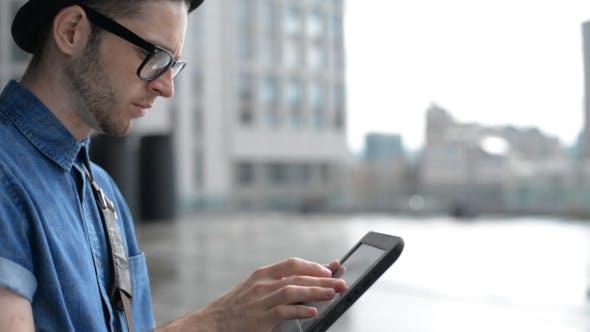 Thumbnail for Using Tablet on Street