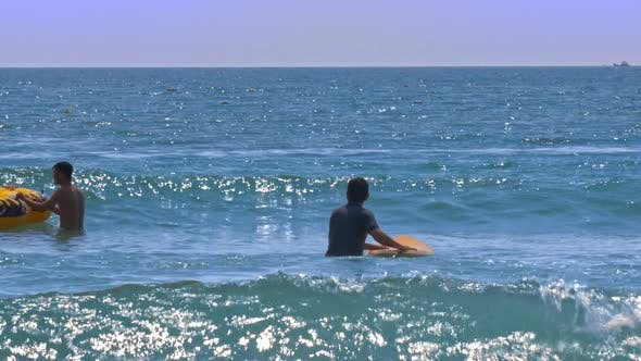 Thumbnail for Guy Beginner Goes Into Ocean Holds Board Waits Wave
