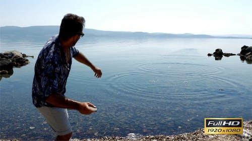 Man Throws Stone To The Sea