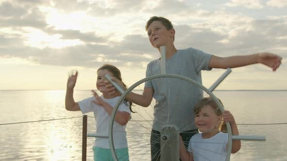 Thumbnail for Children at an Imaginary Steering Wheel at Sunset. Happy Childhood
