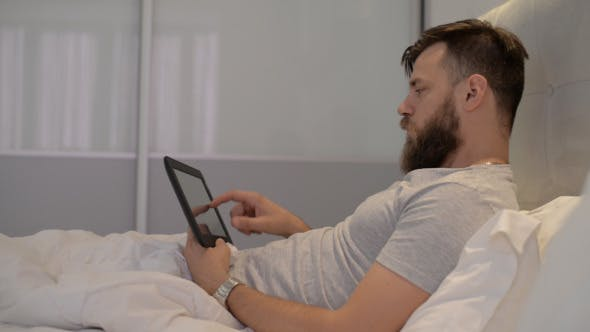 Thumbnail for Man Using Tablet in Bed