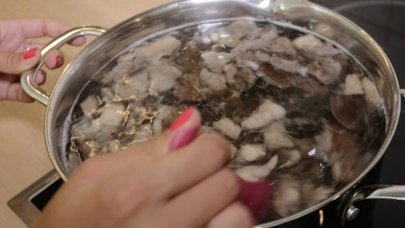 Woman Mixing Spoon Mushroom Soup In a Saucepan.