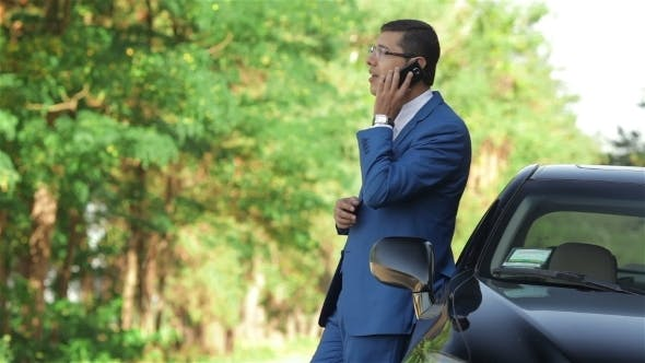 Thumbnail for Businessman Writes a Sms Beside The Car