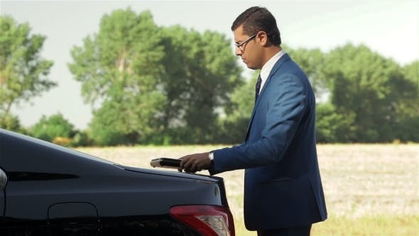 Thumbnail for Businessman Working On The Computer Next To Car