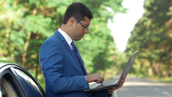 Cover Image for Businessman Working On The Computer Next To Car