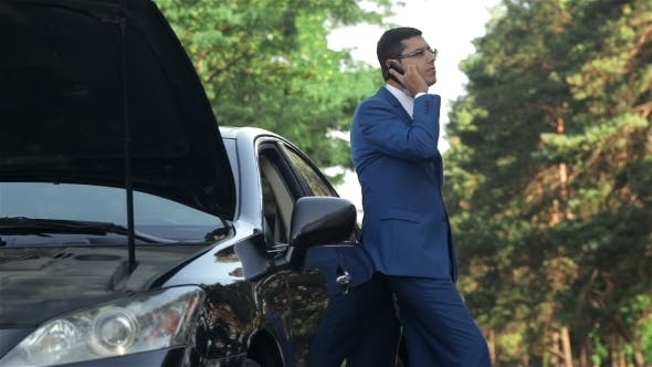 Thumbnail for Businessman On a Mobile Phone Next To a Broken Car