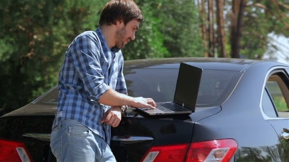 Thumbnail for Man Working On The Computer In The Trunk Of Car