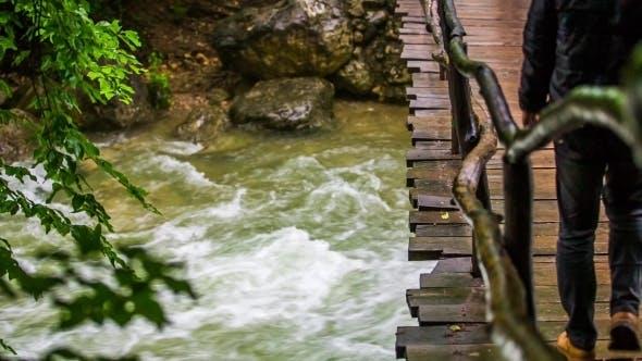 Thumbnail for Man Walking On Bridge Hanging Above Rough River