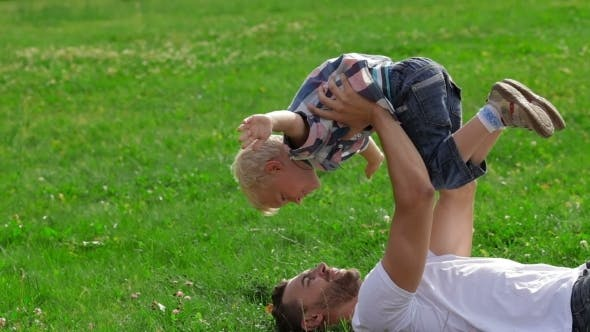 Thumbnail for Father And Son Playing On The Grass In Park