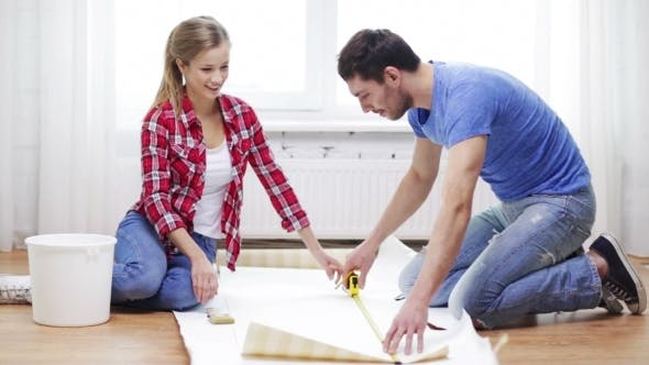 Cover Image for Happy Couple Cutting Wallpaper With Knife At Home