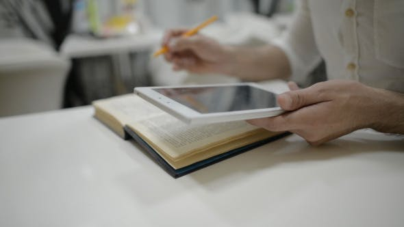 Thumbnail for Man Using Tablet and Book