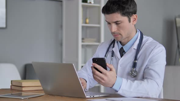 Thumbnail for Doctor Working on Laptop and Using Smartphone