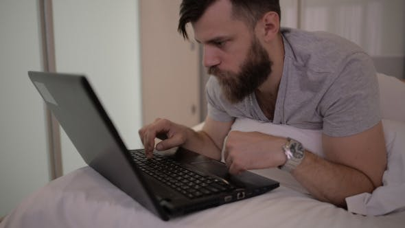 Thumbnail for Beard Man Using Laptop in Bed